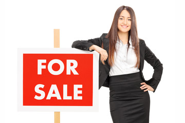 Female realtor leaning on a for sale sign