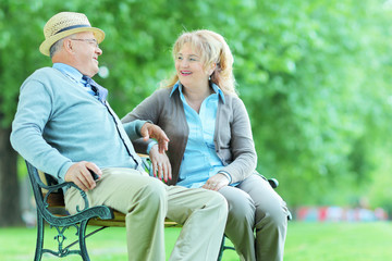 Mature couple talking seated in park