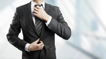 businessman corrects tie
