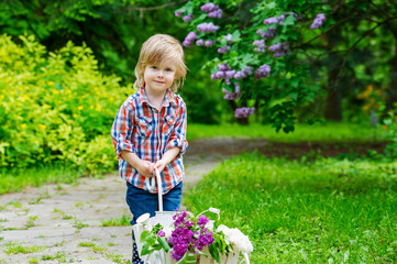 Kid in the garden with a cart full of spring lilac flowers