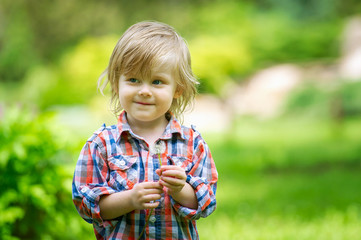 Portrait of an adorable child holding dandelion