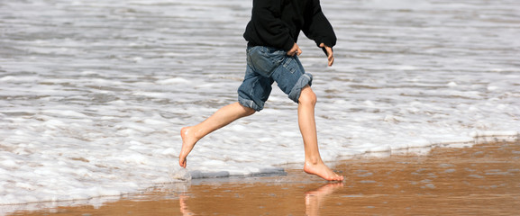 Young Boy Running Feet Ocean Beach Surf Crashing Sea Foam