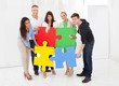 Confident Businesspeople Joining Puzzle Pieces