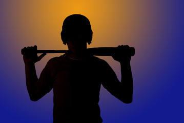 Sun silhouette image of baseball player holding bat