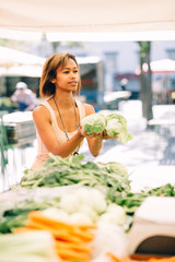 Young woman buying produce at farmers market
