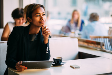 Pensive black businesswoman using tablet computer in coffee shop