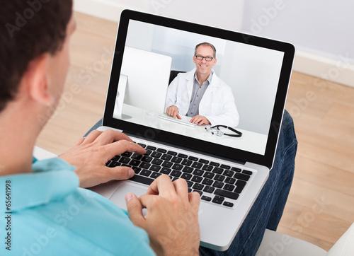 Leinwanddruck Bild Man Having Video Chat With Doctor