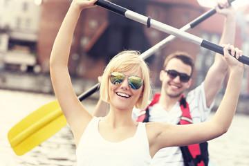Joyful couple canoeing in the river