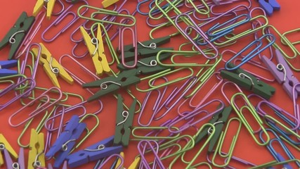 Coloured  paper clips rotating on a red background.