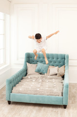 Young boy jumping high on couch at home