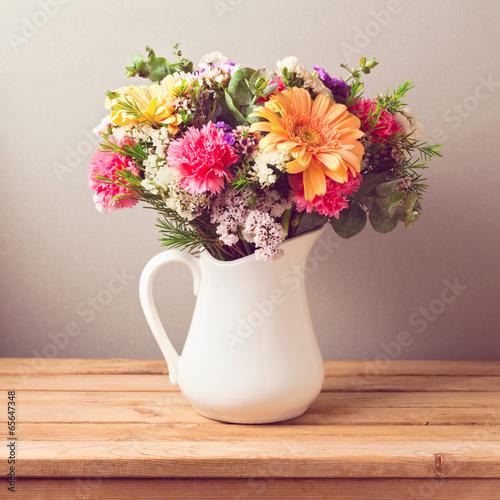 Foto op Canvas Madeliefjes Flower bouquet in white jug on wooden table