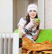 woman in hat with cup near warm radiator