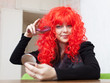 Woman combs red wig