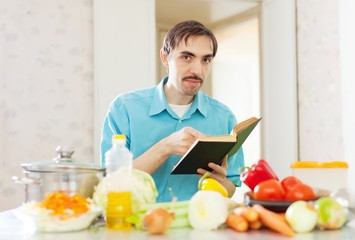handsome  man cooking  vegetables with cookbook