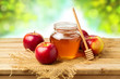Honey and apples on wooden table over bokeh background