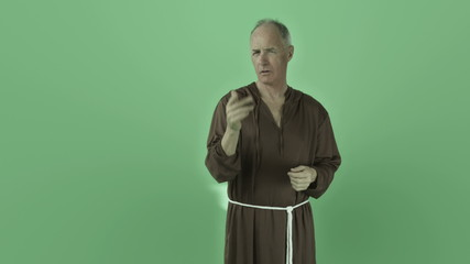 Senior caucasian monk isolated on chroma green screen interview