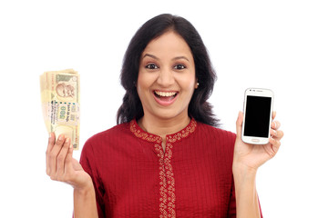 Excited young woman holding Indian currency and mobile phone