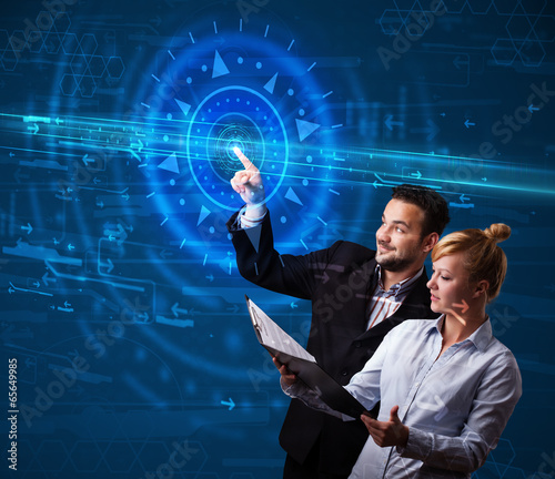Young tech couple pressing high technology control panel screen