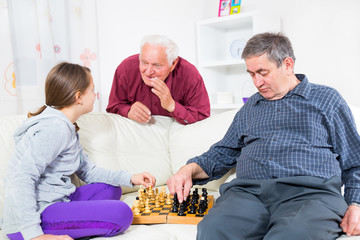 portrait of a girl and grandfather playing chess at home
