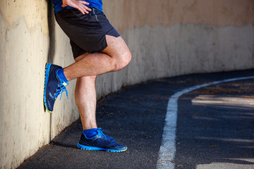 Male runner leaning relaxed against wall.