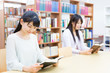 young asian women reading a book in the library