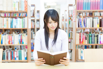 young asian woman reading a book in the library