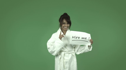 indian woman in bathrobe isolated on green with hire me sign