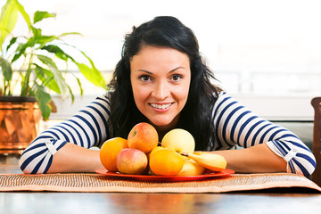 Pretty young woman, smiling in front of the fruit basket .
