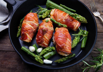 chicken fillet wrapped in prosciutto ham on cast iron frying pan