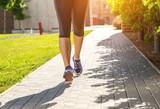 Fototapeta Running woman  (half body photo) on the sidewalk