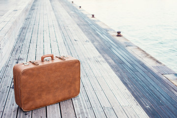 brown vintage suitcase and dock background