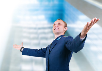 Happy young man aircraft pilot over glass modern building