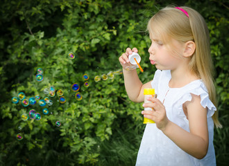 Little girl blowing soap bubbles in the park.