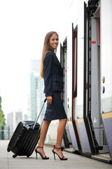 Business woman traveling on train with suitcase