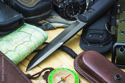 Knife surrounded by tourist equipment