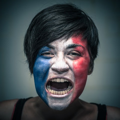 Angry woman with flag of France painted on face