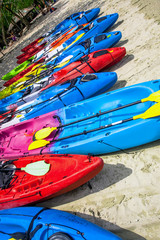 colorful kayaks lined in a row on a white sand beach