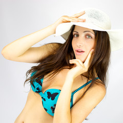 Beautiful female model with hat and bikini in studio