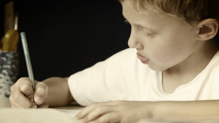 Little boy diligently writes his homework: black and white style