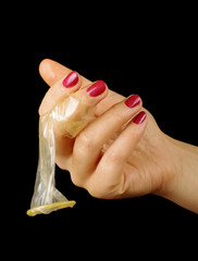 Female hand holding condom isolated on the black background
