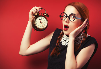 Surprised redhead girl with clock.