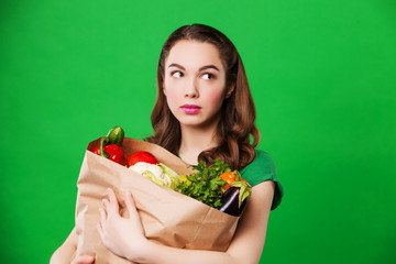 beautiful woman holding a grocery bag full healthy food. looking