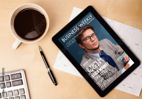 Foto op Canvas Koffie Tablet pc showing magazine on screen with a cup of coffee on a d