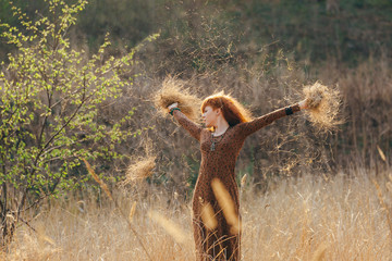 Young woman walking in golden dried grass field