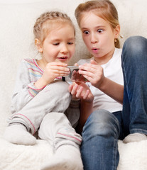 Surprised children with mobile phone