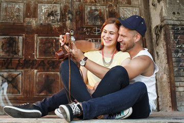 Young couple in embrace takes selfie with an old camera