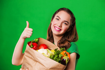 beautiful happy woman holding a grocery bag full of fresh and
