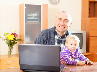 father and baby  at  laptop