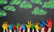 angemalte Kinderhände vor Kreide-Wolkenhintergrund