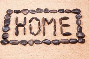 word home written with pebbles on the sand of a beach